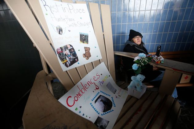 A woman sits beside posters of Hunter Haze Straight-Smith, the three-year-old who was allegedly stabbed...