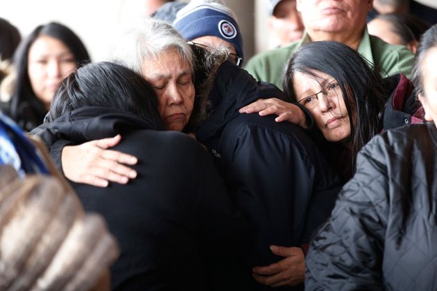 The mother, centre left, of Hunter Haze Straight-Smith is comforted at a vigil outside Winnipeg's Childrens