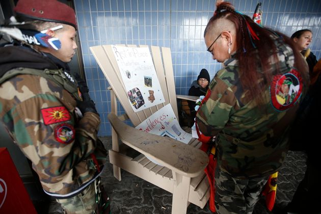 Members of the First Nation Indigenous Warriors look at posters of Hunter Haze