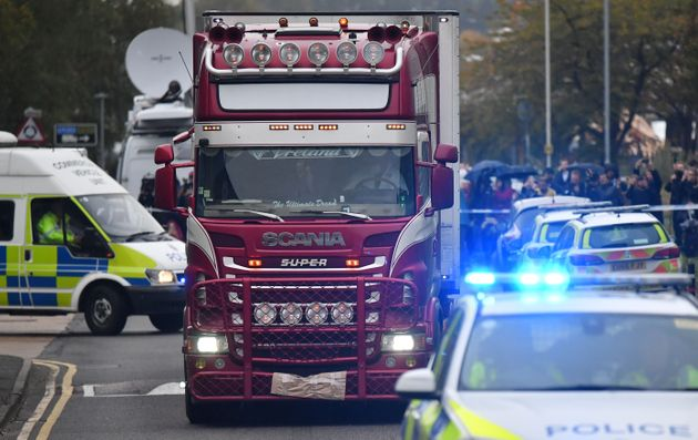 Police officers drive away a lorry (C) in which 39 dead bodies were discovered sparking a murder investigation...
