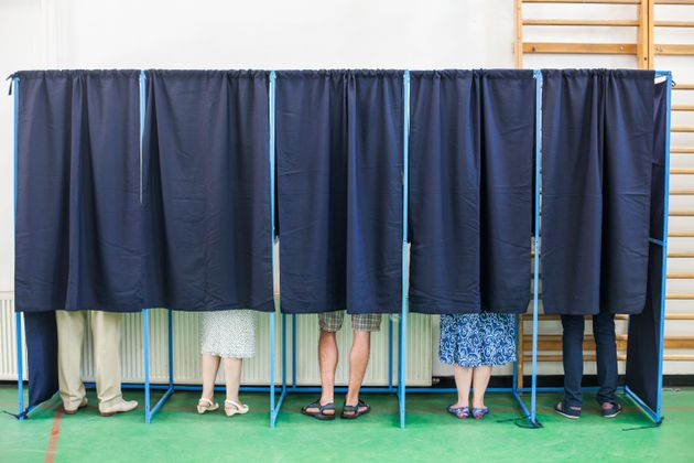 Color image of some people voting in some polling booths at a voting