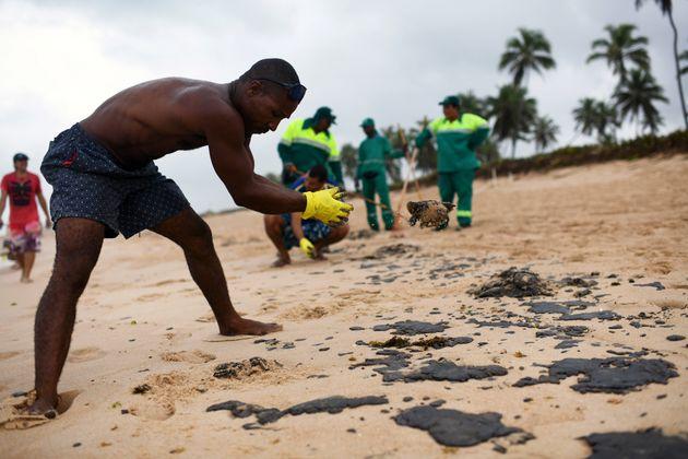 Um morador trabalha para remover um derramamento de óleo que contaminou a praia de Barra de Jacuipe,...
