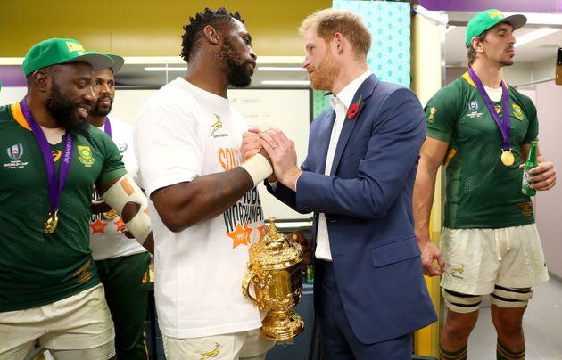 南アフリカ代表のロッカールームを訪れ、優勝カップを持つコリシ主将をたたえるヘンリー王子