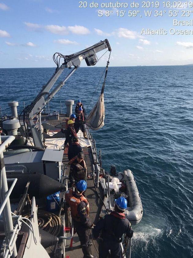 Marinha usa guindaste para recolher petróleo em alto