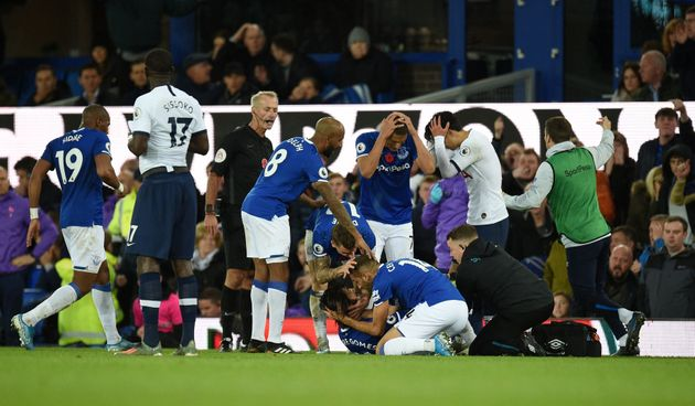 Teammates comfort Everton's Portuguese midfielder André Gomes (C floor) as he gets attention for an injury...