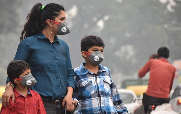A woman and children wearing anti-pollution masks to protect against air pollution at Old Railway Road...