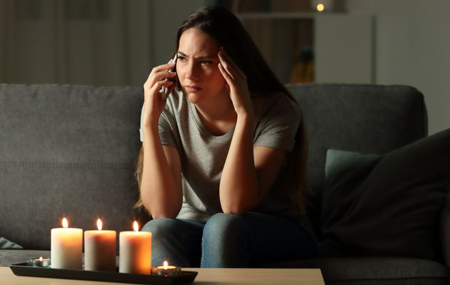 Worried woman talking on phone during blackout sitting on a couch in the living room at
