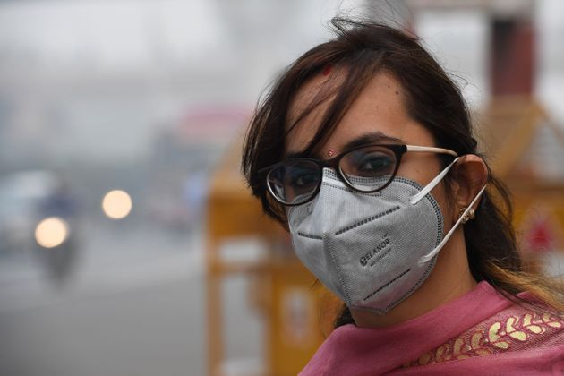 A woman wearing a protective face mask waits for public bus in New