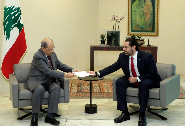 Lebanese President Michel Aoun, left, receives a letter of resignation from Prime Minister Saad Hariri, at the presidential p