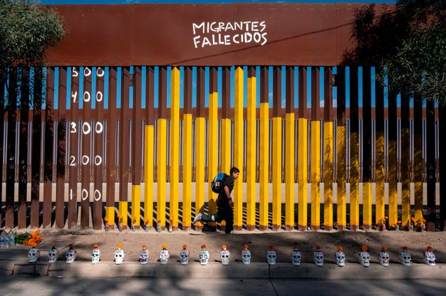 Junior Hernandez, a migrant from Guatemala, runs next to the border fence where he and members of the...