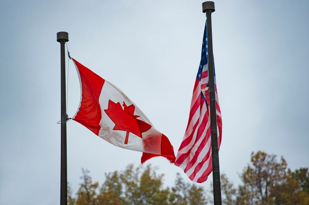 Close-up view of an American flag and a Canadian flag waving in the