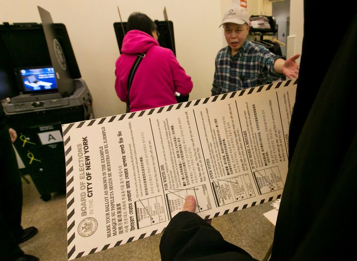 In this Nov. 4, 2014 file photo, a voter carries her ballot to be scanned at a polling place in New York's Chinatown neighbor