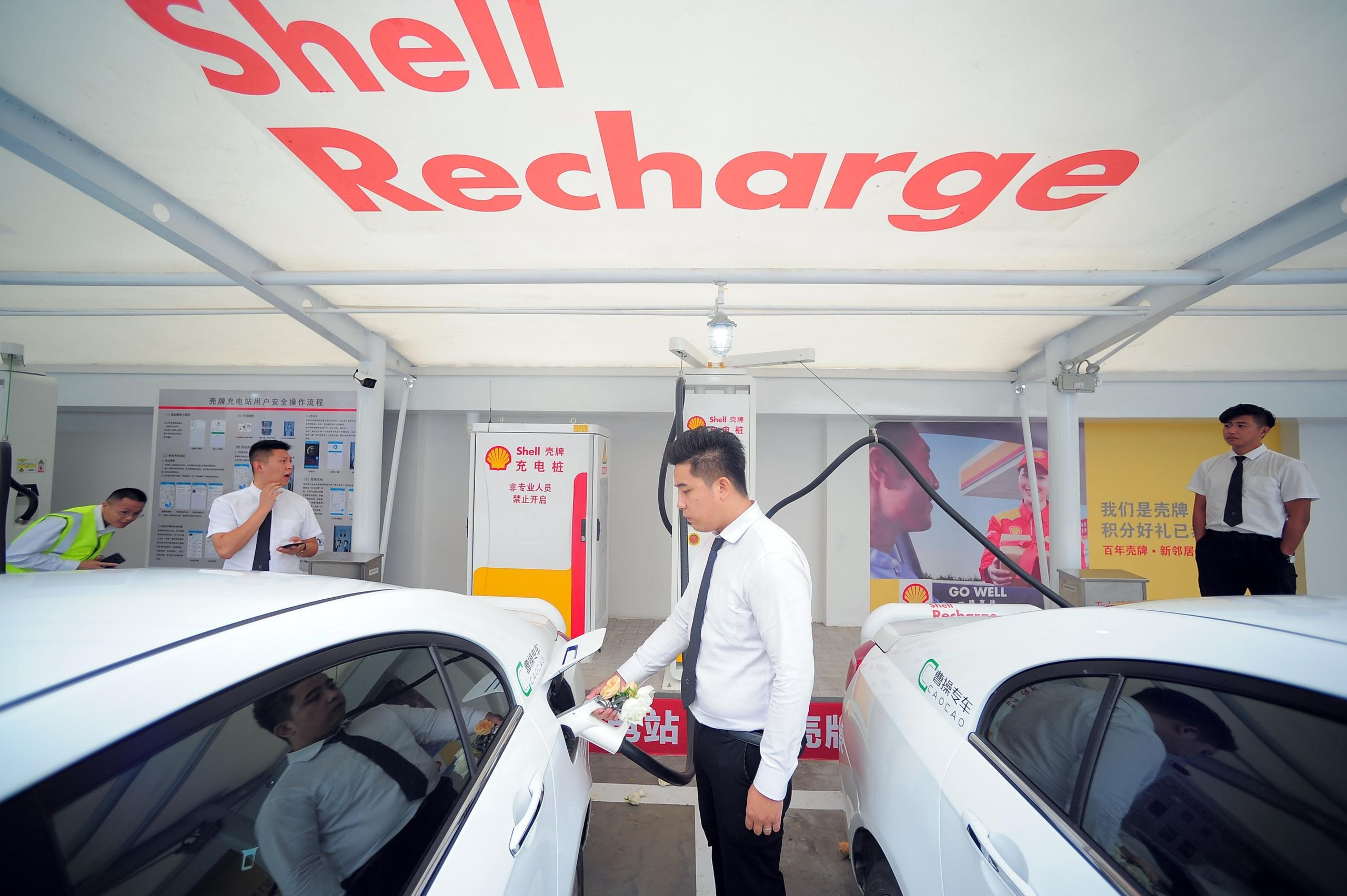 A worker charges an electric car at a Shell charging station on September 28, 2018 in Tianjin, China.