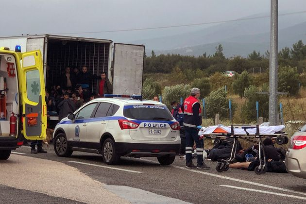 Migrants are seen inside a truck found by police, as ambulance staff arrive to the scene near the town...