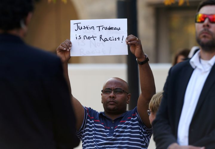 "A man holds a sign that reads ""Justin Trudeau is not racist"" as the Liberal leader spoke in Winnipeg on Sept. 19, 2019."