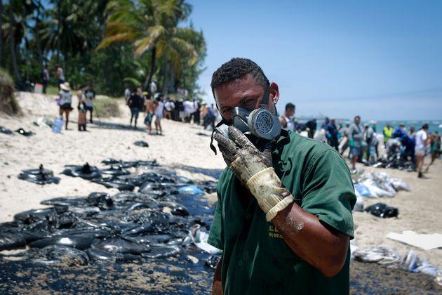 Trabalhador municipal ajuda a remover óleo da praia de Paiva, em Cabo de Santo Agostinho