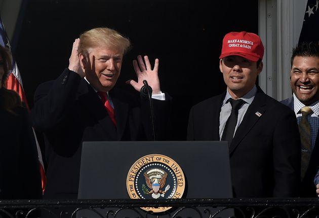 US President Donald Trump reacts as player Kurt Suzuki wears a
