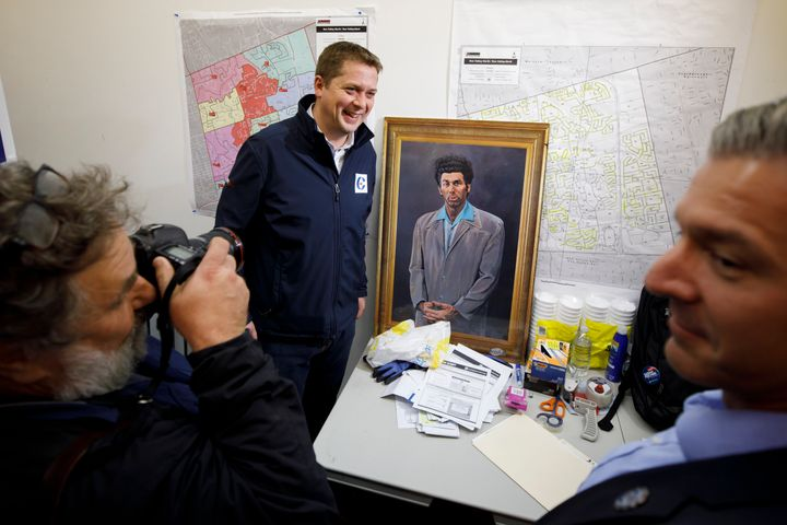 "Andrew Scheer poses beside a portrait of ""Seinfeld"" character Kramer during a campaign stop on Oct. 19, 2019 in North York, Ont."