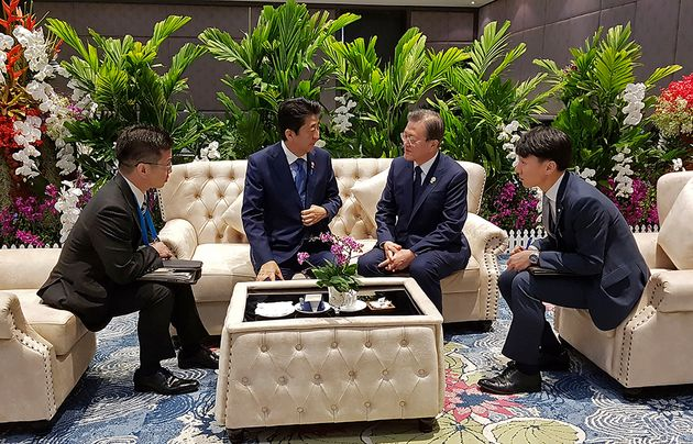In this photo provided by South Korea Presidential Blue House, South Korean President Moon Jae-in, center...