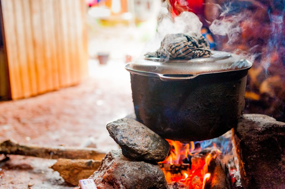 smoking iron pot above fire in traditional african kitchen in cameroon during