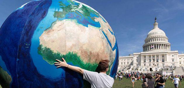 Un joven sostiene un globo terráqueo gigante frente al Capitolio de EEUU para protestar contra el cambio
