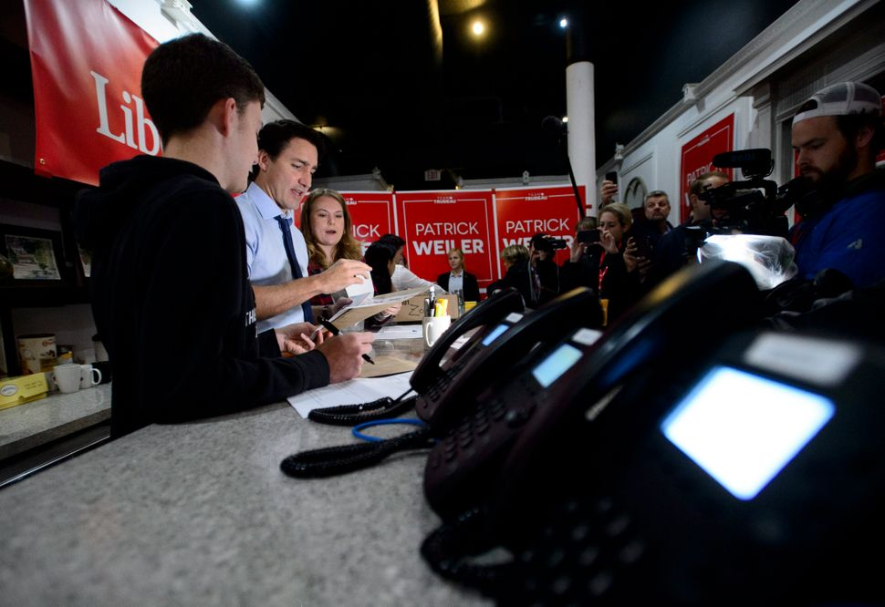 Liberal Leader Justin Trudeau works with volunteers Nicola Cox and Christian Gomes as he makes a campaign...