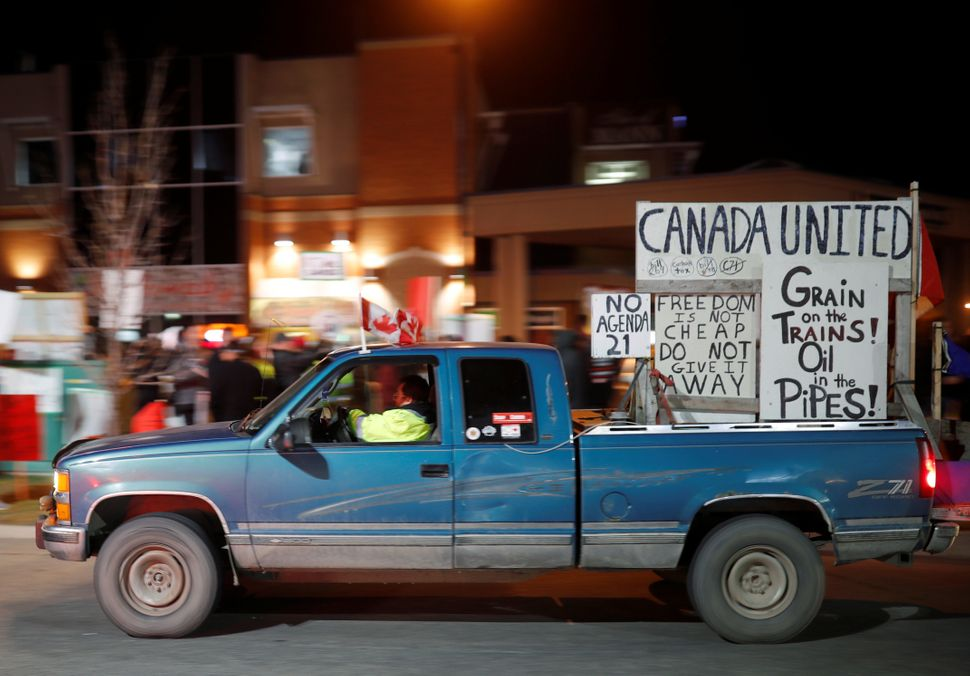 Protesters gather outside a campaign rally for Liberal Leader Justin Trudeau in Calgary on Oct. 19,
