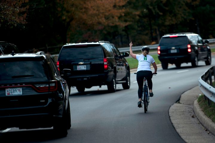 Juli Briskman shows her middle finger as a motorcade with President Donald Trump departs Trump National Golf Course in Sterling, Virginia, in 2017. Two years later, Briskman is on the ballot for local office.
