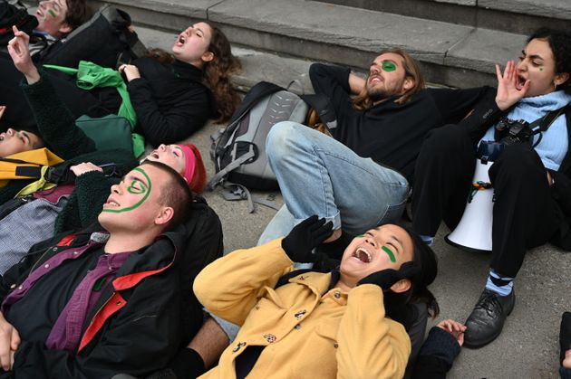 High school students lie on the ground as they protest climate change in front of the Canadian prime...