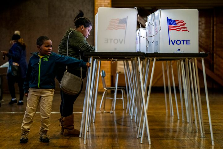 Amari Hardy, 7, plays alongside his mother, TaQuisha Hardy, of Flint, as she casts her ballot on Election Day,  Tuesday, Nov.