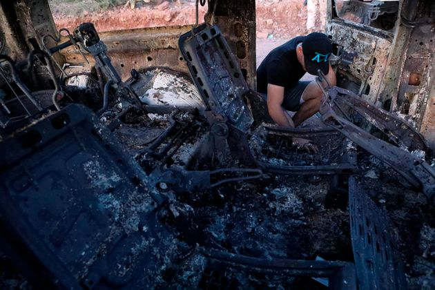 A family member looks at a car that was ambushed and burned by a drug cartel in the Sonora mountains,...