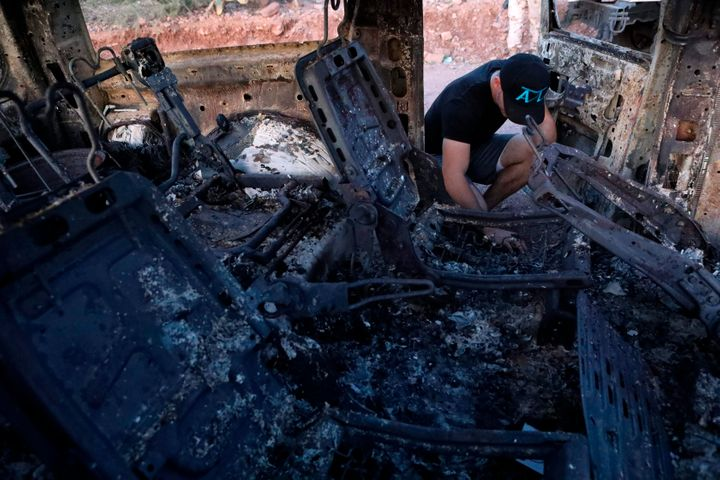 A family member looks at a car that was ambushed and burned by a drug cartel in the Sonora mountains, Mexico, on Nov. 5, 2019