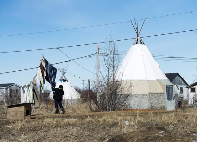 An indigenous women takes down laundry in the northern Ontario First Nations reserve in Attawapiskat,...