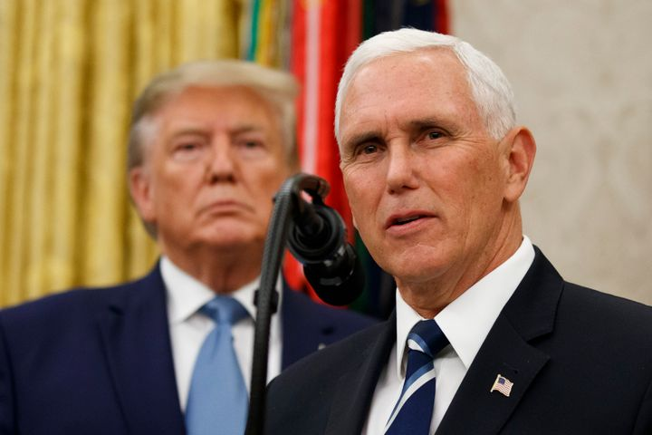 Vice President Mike Pence, right, speaks with President Donald Trump behind him, during a ceremony to present the Presidentia