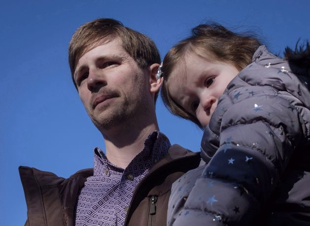 Edouard Maurice speaks to reporters outside court while holding his daughter Teal in Okotoks, Alta. on...