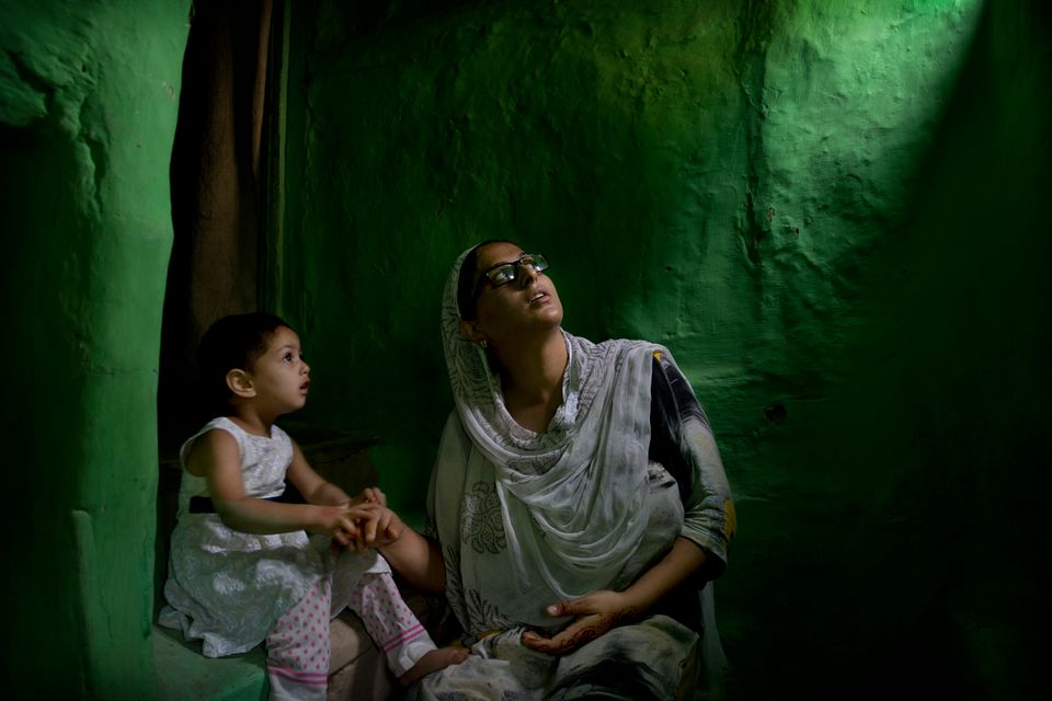 In this Sept. 27, 2019, photo, Sumaira Bilal, wife of Kashmiri detainee Bilal Ahmed, talks to her two-year-old...