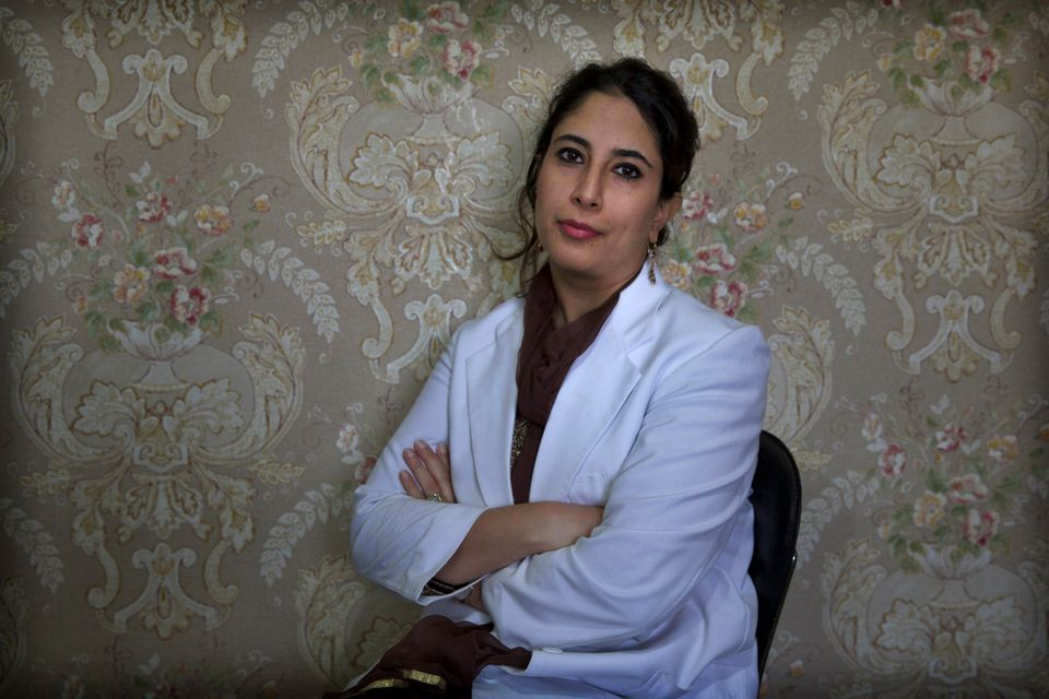 In this Sept. 27, 2019, photo, a Kashmiri doctor Sabahat Rasool sits for a photograph inside her clinic...