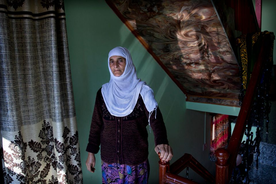 In this Friday, Oct. 14, 2019, photo, a Kashmiri woman Biba Malla stands for a photograph inside her...