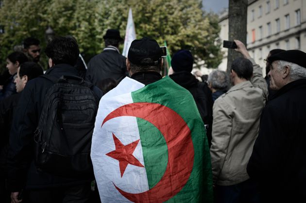 A man wearing the Algerian national flag takes part in a protest against political repression in Algeria,...