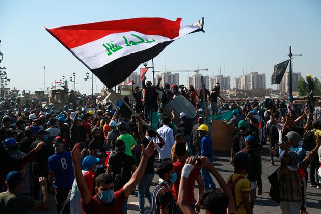 Anti-government protesters try to cross the al- Shuhada (Martyrs) bridge in central Baghdad, Iraq, Wednesday,...