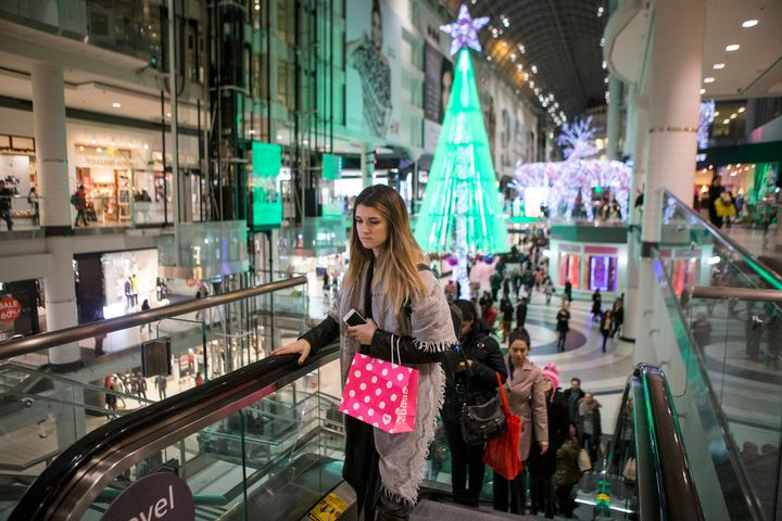 Holiday shoppers make their way through Toronto's Eaton Centre on Dec. 14, 2015. A new survey found nearly half of Canadians overspent on holiday purchases last year.