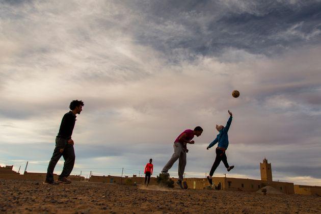 Des jeunes jouant au football dans les rues de