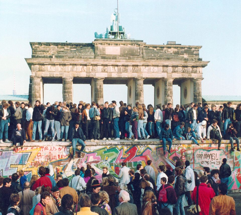 Germans from East and West stand on the Berlin Wall in front of the Brandenburg Gate in Berlin, 10 November 1989.