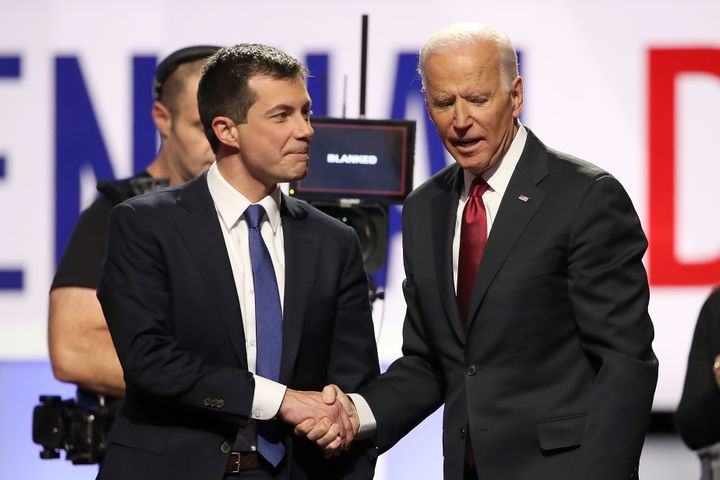 Buttigieg greets Joe Biden before a presidential primary debate on Oct. 15. Biden has run heavily on his ties to Obama, but B