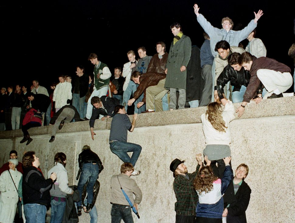 People climb the Berlin wall at the Brandenburg Gate as they celebrate the opening of the East German...