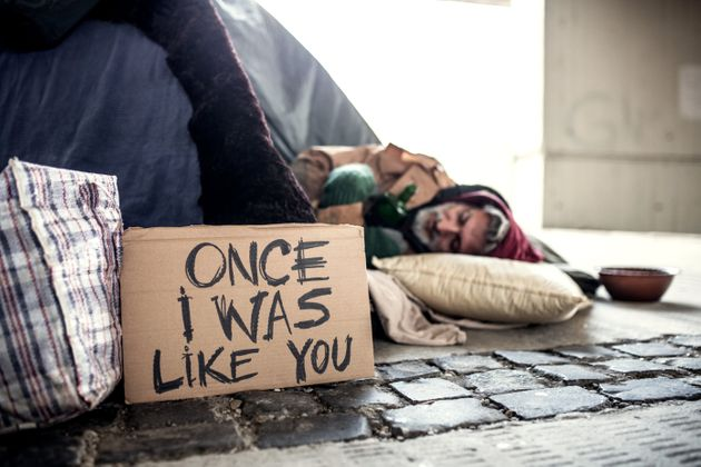 A homeless beggar man lying on the ground outdoors in city asking for money donation, sleeping.