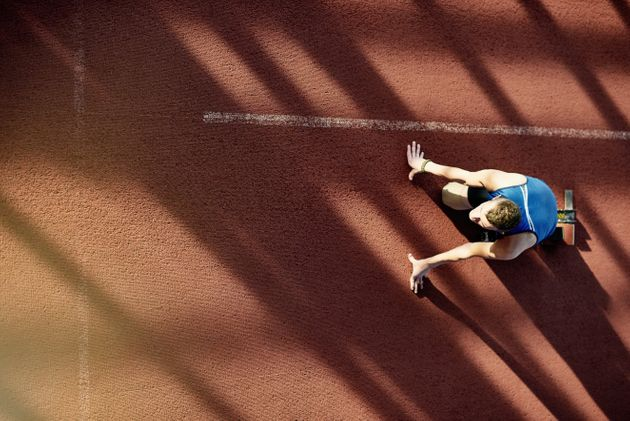 Above view image of dedicated amputee athlete with prosthetic leg in start position on running