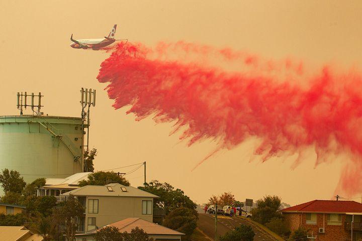 A water bombing plane drops fire retardant on a bushfire in Harrington.