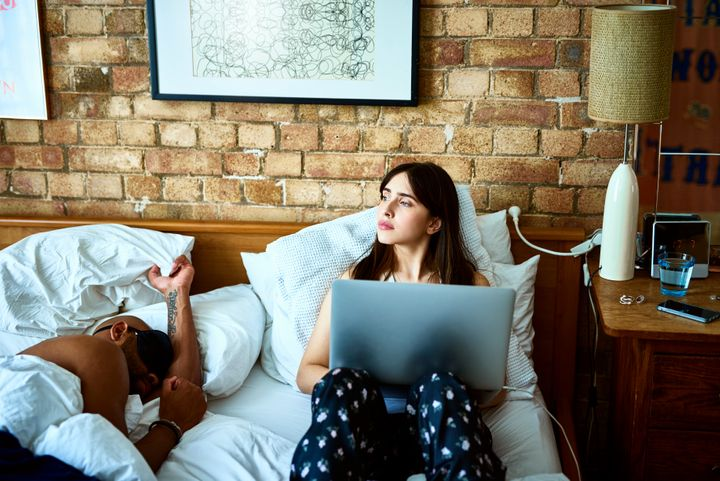 Couple in bedroom, man lying down sleeping as woman works on computer and looks out of the window
