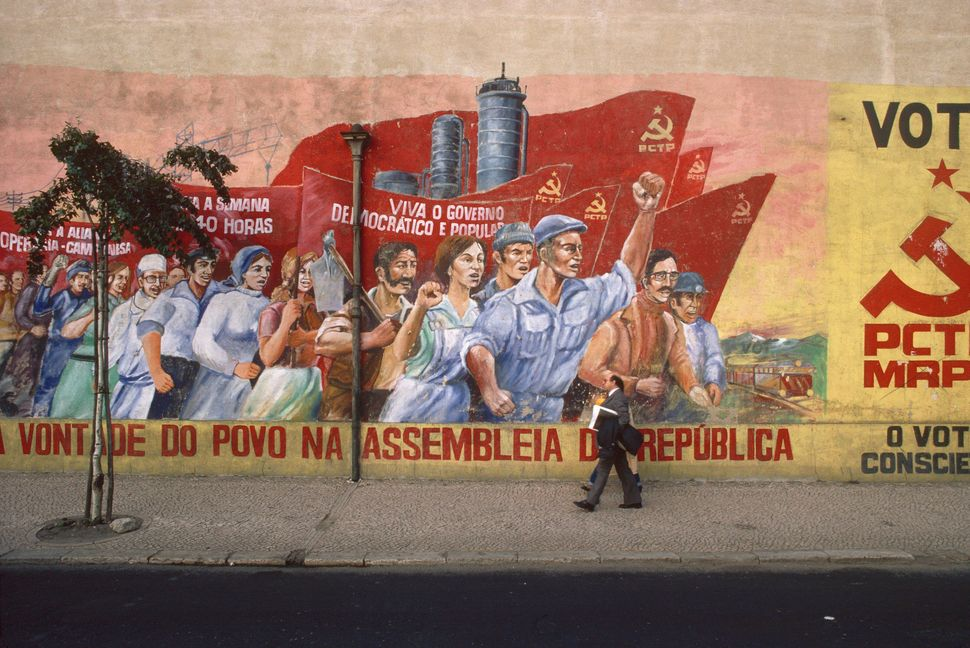 People walk by a mural evoking the Carnation Revolution in Lisbon, Portugal on Jan. 1, 2000.